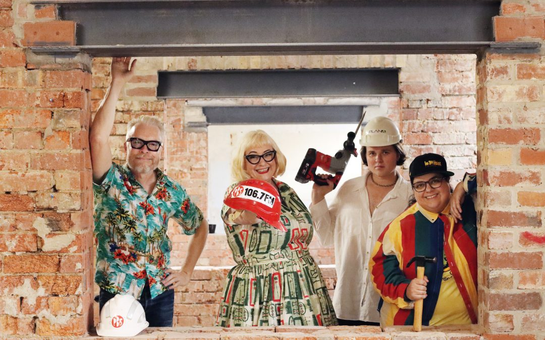 Four people in a brick building with construction equipment and hard hats