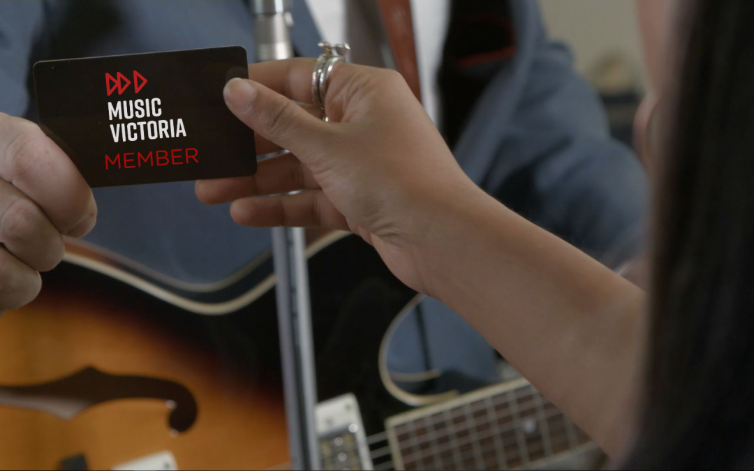 """Black membership card reading """"Music Victoria member"""" being handed to a person holding a guitar"""