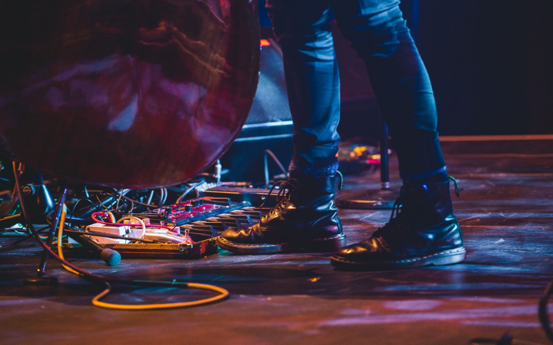 Person in Doc Marten boots is standing on stage playing an electric double bass