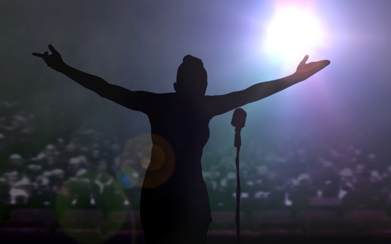 Person standing on a stage in front of a microphone with a spotlight shining down on them
