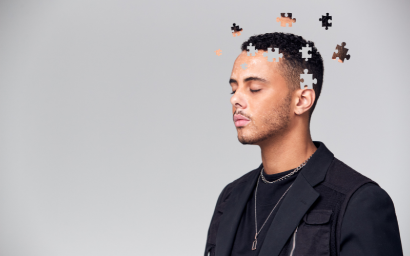 A young man is standing with his eyes closed against a plain grey background. He looks as though he is meditating or in deep thought. Puzzle pieces are circling his head. He is wearing a black top and jacket